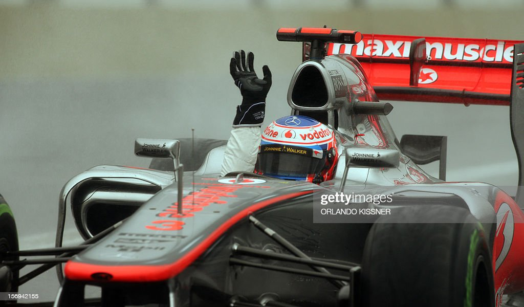 British Formula One driver Jenson Button waves from the car celebrating his victory on the Brazil's F-1 GP, on November 25, 2012 at the Interlagos racetrack in Sao Paulo, Brazil. AFP PHOTO