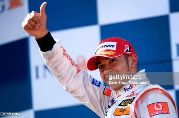 British Formula One driver Lewis Hamilton celebrates on the podium after finishing third in his McLaren MP4-22 Formula One car during the 2007...