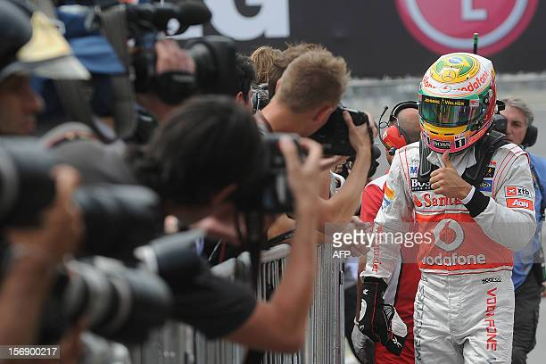 British Formula One driver Lewis Hamilton of McLaren gestures to celebrate the pole position for the Brazilian GP at the Interlagos racetrack in Sao...