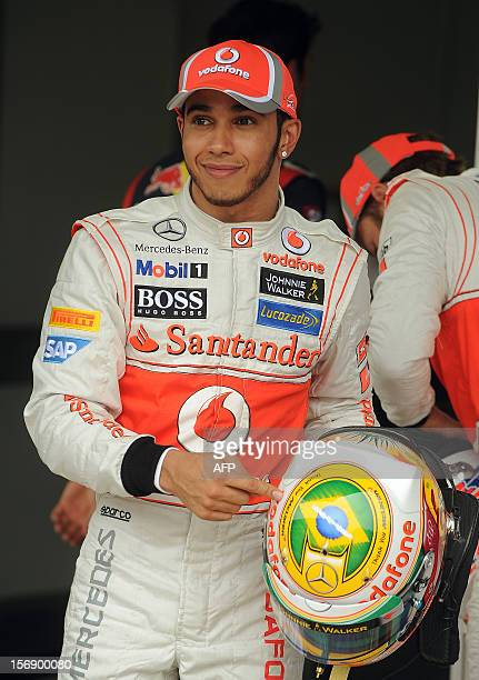 British Formula One driver Lewis Hamilton of McLaren points at a Brazilian flag on his helmet after getting the pole position for the Brazilian GP on...