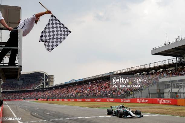 TOPSHOT British Formula One driver Lewis Hamilton of Mercedes AMG GP crosses the finish line during the German Formula One Grand Prix at the...