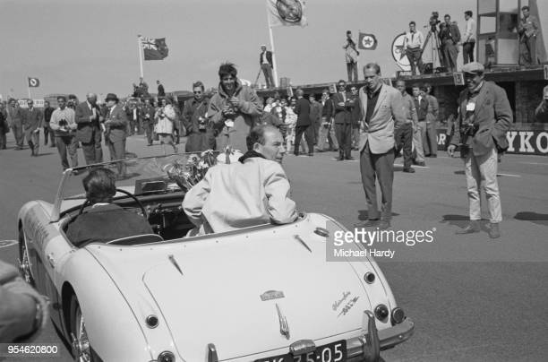 British Formula One driver Stirling Moss sitting in the back of a car after the Dutch Grand Prix, in which he placed fourth but first in the Drivers'...