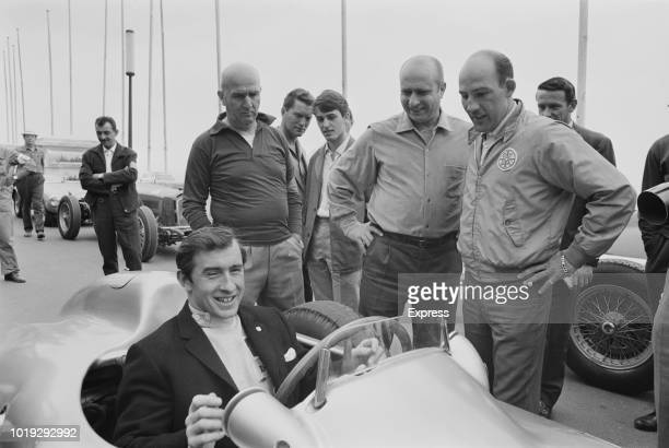 British formula One racing driver Jackie Stewart on board a racing car smile with British Formula One racing driver Sirling Moss, Argentine racing...