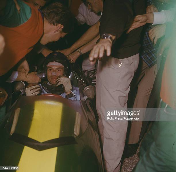British Formula One racing driver Jim Clark is surrounded by spectators and fans while still in his LotusClimax 25 Formula One car after victory in...