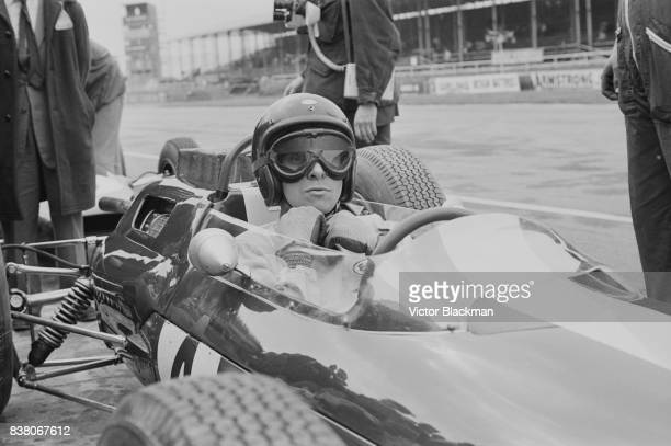 British Formula One racing driver Jim Clark , on the Team Lotus, Lotus 25 Climax V8, makes a pit stop during the British Grand Prix at Silverstone,...