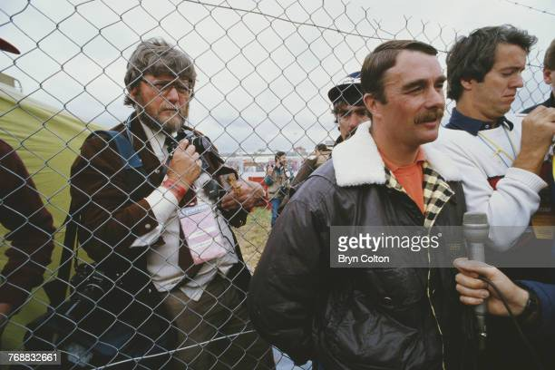 British Formula One racing driver Nigel Mansell is pressed back against a wire fence by the media as he holds an impromptu press conference after...