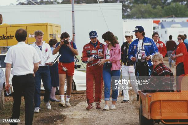 British Formula One racing driver Nigel Mansell of the WilliamsHonda team signs an autograph for a fan as he walks back to the pitlane before the...