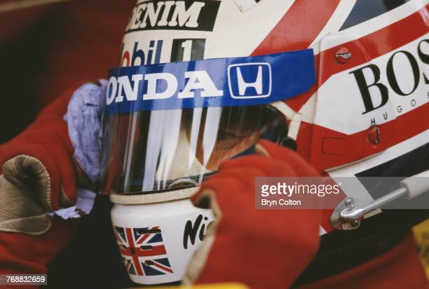 British Formula One racing driver Nigel Mansell wipes his visor as he sits in his car on the starting grid at the 1986 Australian Grand Prix at the...