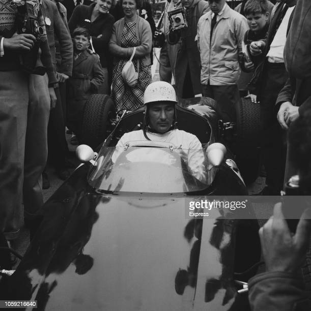 British Formula One racing driver Stirling Moss on his Cooper T53 Climax S4 team RRC Walker Racing Team surrounded by supporters following his win at...