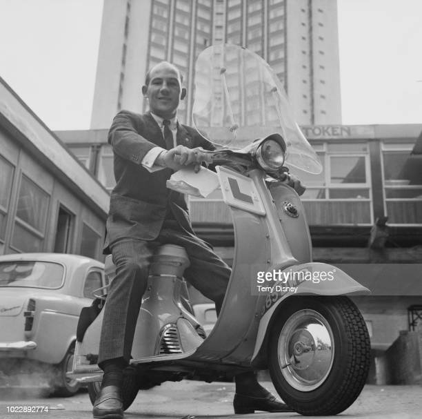 British formula One racing driver Stirling Moss pictured seated on a Triumph Tina motor scooter with learner plates as he prepares to take a...