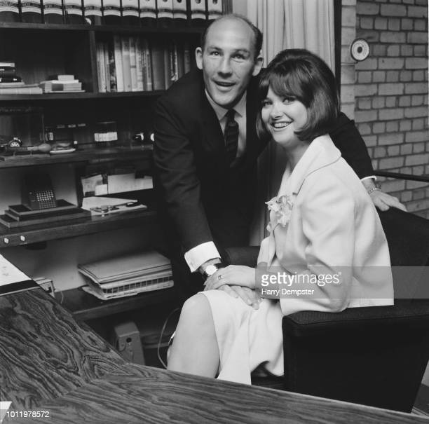 British Formula One racing driver Stirling Moss pictured with his wife Elaine Barberino in the office of his Mayfair home in London on 26th June 1964