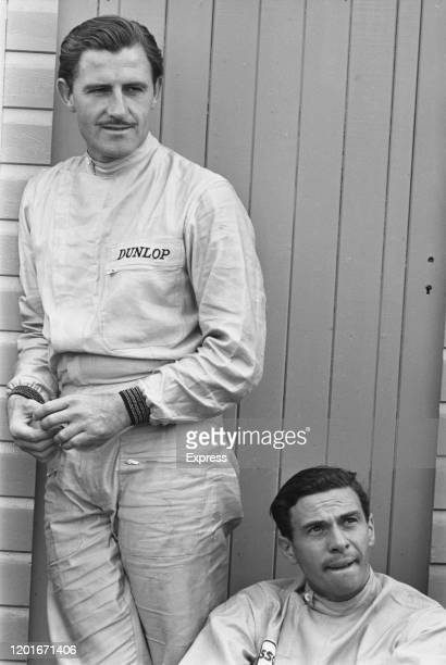 British Formula One racing drivers Graham Hill and Jim Clark taking a break at the International Car Race meeting, organised by the British Racing...