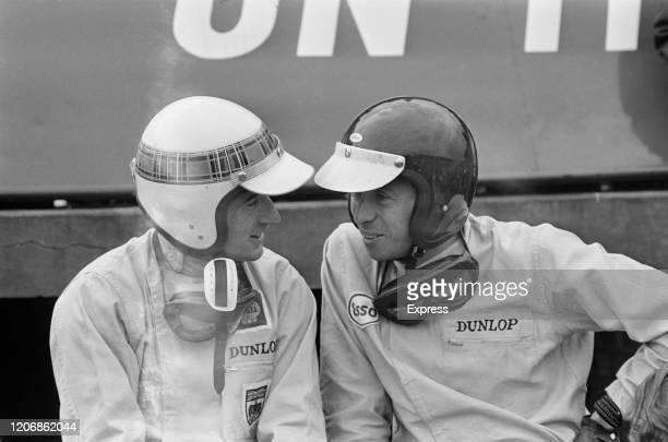 British Formula One racing drivers Jackie Stewart and Jim Clark in conversation on race day for the 1965 British Grand Prix at Silverstone...
