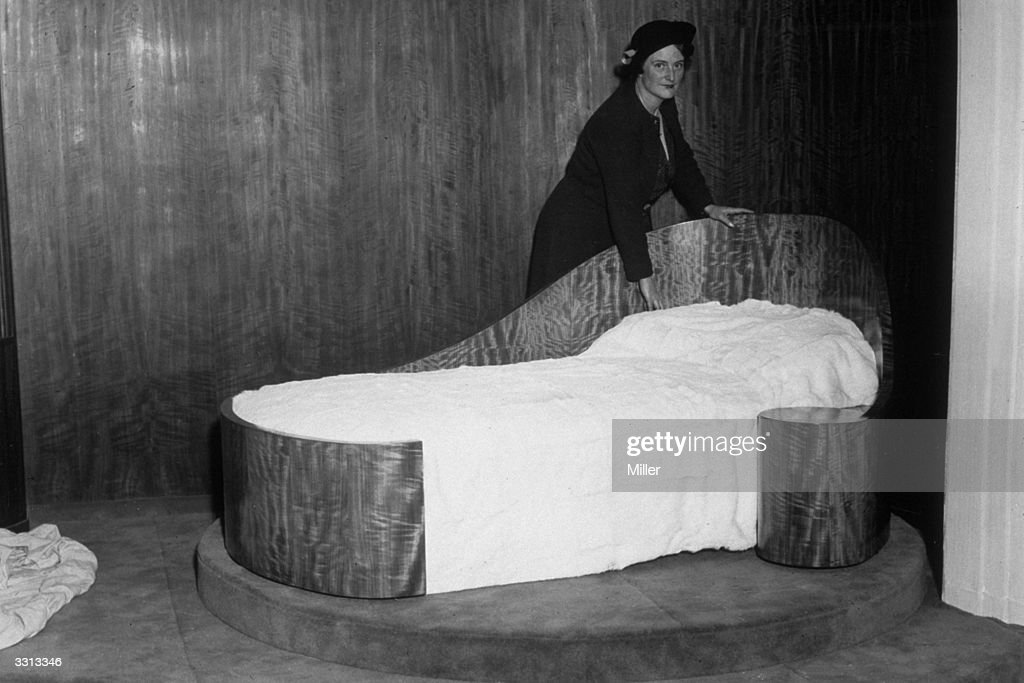 British furniture, textile and interior designer, Betty Joel (1894 - 1985) standing beside her revolving bed at the Royal Academy's exhibition of British Art in Industry, January 1935.