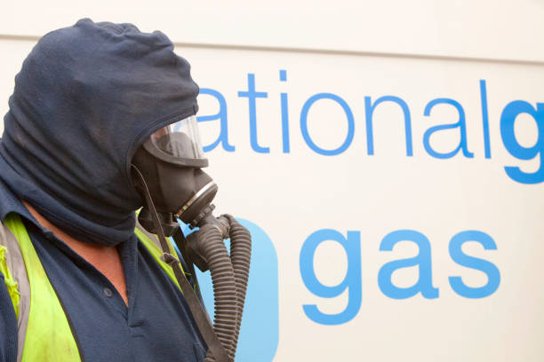 A British Gas worker wears protective gas mask prior to cutting through the gas main as part of an upgrade of piping, Ambleside, Cumbria, UK.