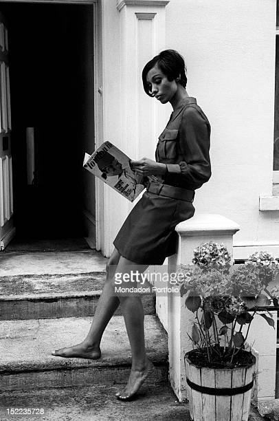 A British girl barefoot and in miniskirt reading a number of the magazine 'London Life' She wears a makeup in the Mary Quant style London 1960s