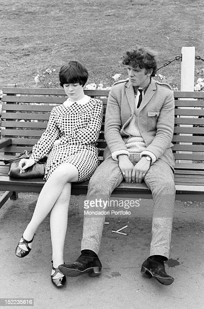 A British girl in minidress smoking a cigarette on a bench beside a British boy London 1960s