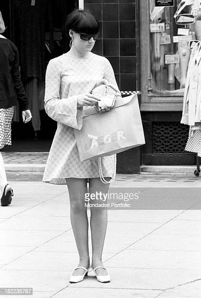 British girl in minidress waiting on the pavement with a shopping bag of the clothes shop 'Jaeger' London 1960s