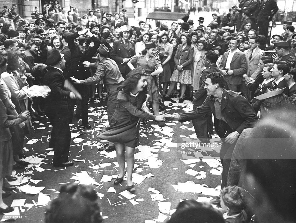 British girls, of the Picture Division of the London Office of War Information dance in the street with American soldiers during the 'V-E Day' celebration in London May 8, 1945.