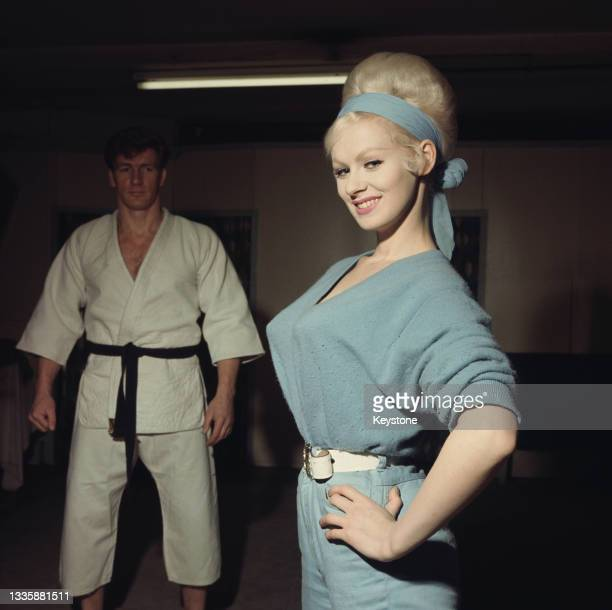 British glamour model and actress Sabrina , wearing a blue jumpsuit with matching headband, and British wrestler, martial artist and actor Joe...