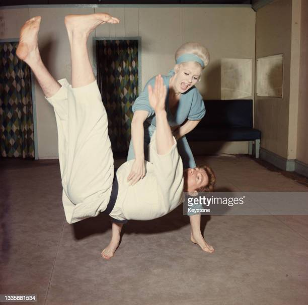 British glamour model and actress Sabrina , wearing a blue jumpsuit with matching headband, throws British wrestler, martial artist and actor Joe...