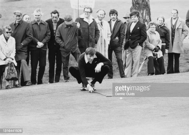 British golfer Peter Oosterhuis watched by spectators lines up his putt on the 15th hole during the Penfold Golf Tournament on 8th May 1974 at the...