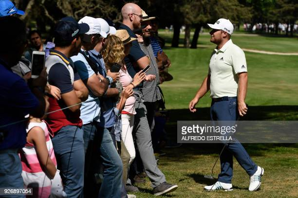 British golfer Tyrell Hatton talks to a friend among the public at green 16 during the third round of the World Golf Championship in Mexico City on...