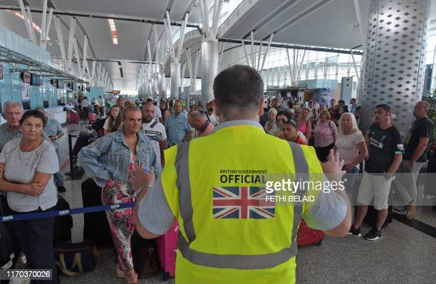 A British government official speaks to tourists flying with Thomas Cook as they queue at the Enfidha International airport on September 23 on the...