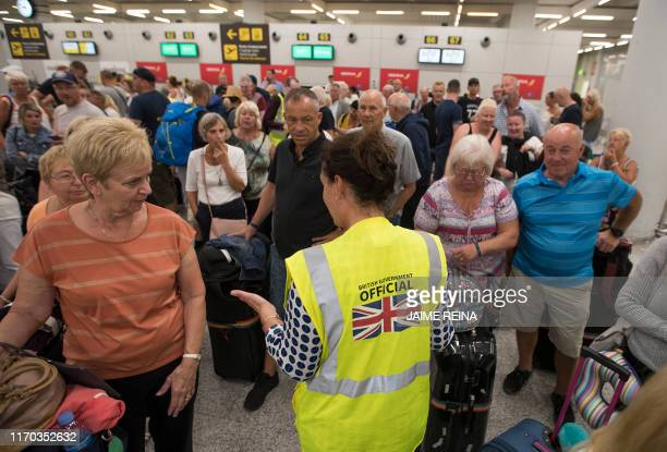 British Government official speaks with passengers of the British travel group Thomas Cook at Son Sant Joan airport in Palma de Mallorca on September...