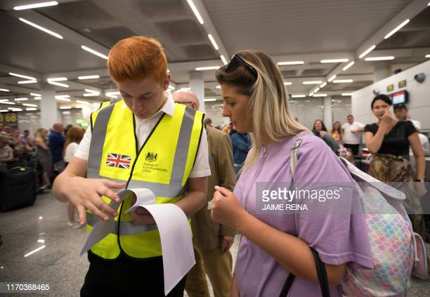 A British Government official talks to a passenger of British travel group Thomas Cook at Son Sant Joan airport in Palma de Mallorca on September 23...