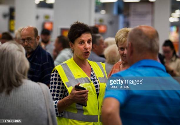 A British Government official talks to passengers of British travel group Thomas Cook at Son Sant Joan airport in Palma de Mallorca on September 23...