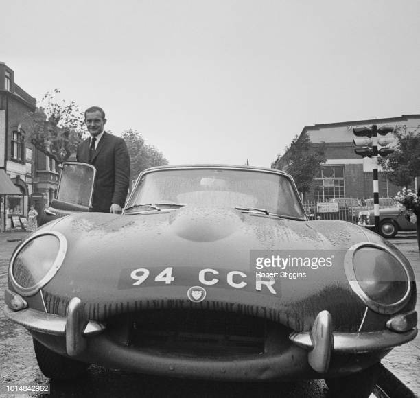 British Grand Prix motorcycle road racer Mike Hailwood with his Jaguar E-Type sports car, Acton Lane, west London, 17th October 1963.