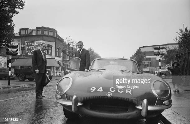 British Grand Prix motorcycle road racer Mike Hailwood with his Jaguar E-Type sports car and the solicitor who will be representing him in a speeding...