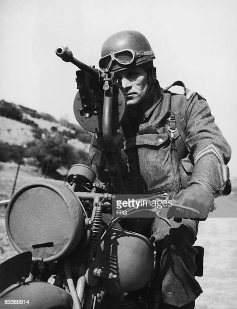 British Grenadier guardsman aiming a Thompson sub-machine gun, which is mounted on his motorcycle, circa 1940.