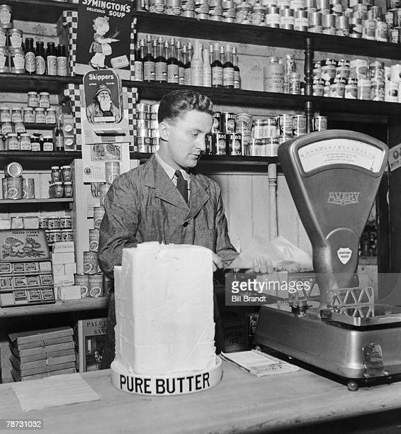 A British grocer weighs a slab of butter in his shop 1942 Original Publication Picture Post 1095 Army Suitability Test unpub
