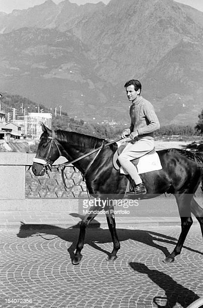 British group captain and aviator Peter Townsend crossing a bridge on horseback. Merano, 1955