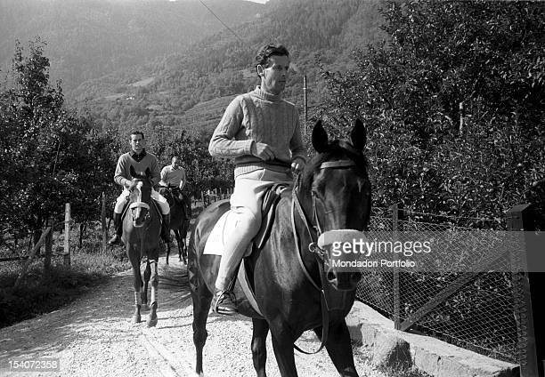 British group captain and aviator Peter Townsend riding a horse on a dirt path. Merano, 1955