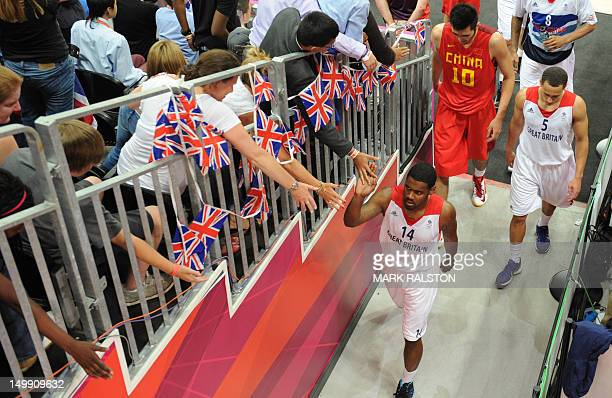 British guard Kyle Johnson cheers with supporters as he leaves at half time during the men's basketball preliminary round match Great Britain vs...