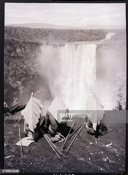 British Guiana South America Photo shows three Guianese men with sunleafhelmets They sit at Kaitur Falls a falls many times higher than Niagara deep...