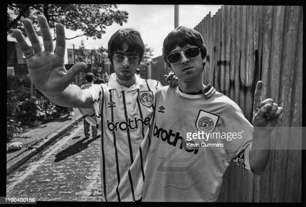British guitarist Noel Gallagher and British singer Liam Gallagher of rock band Oasis wearing Manchester City football shirts, UK, 9th May 1994.