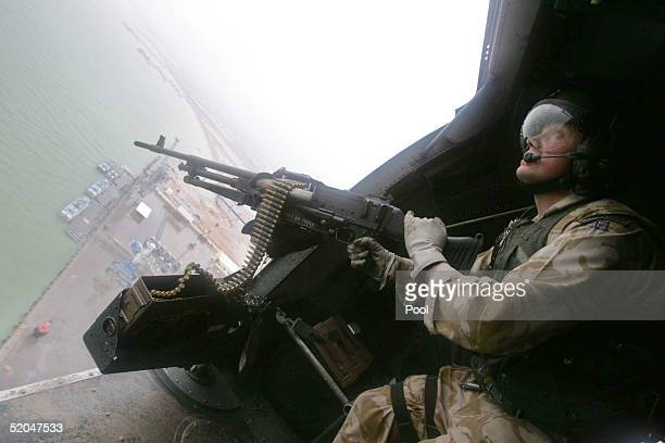 British gunner mans his gun as a military helicopter flies over the water way January 22 2005 in Umm Qasr Iraq Interim Prime Minister Iyad Allawi...