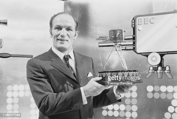 British heavyweight boxer Henry Cooper holds up the 1970 BBC Sports Personality of the Year Award after being presented with the trophy at the annual...