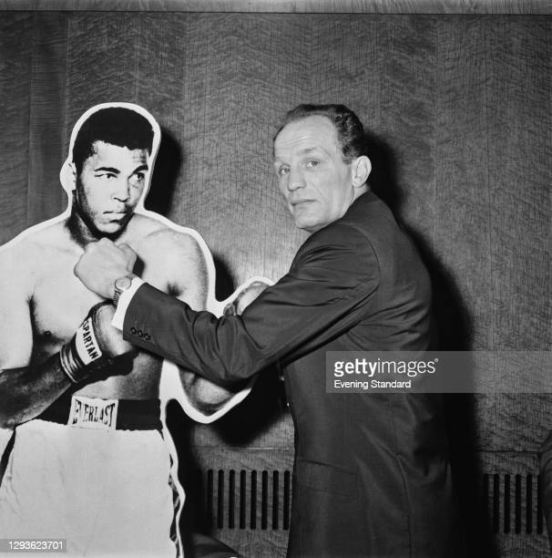 British heavyweight boxer Henry Cooper with a cardboard standee of American boxer Cassius Clay at the Odeon Leicester Square in London, 19th April...