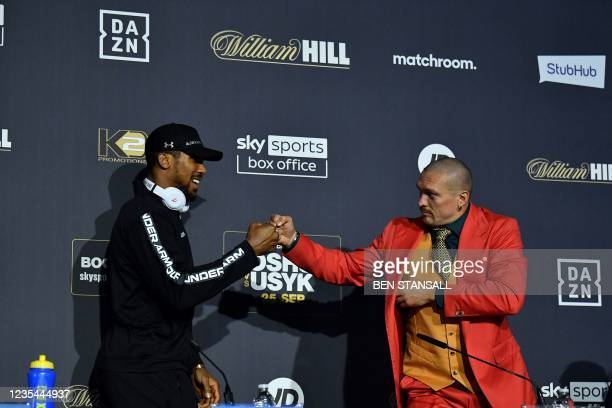 British heavyweight champion boxer Anthony Joshua and Ukraine's Oleksandr Usyk bump knuckles ahead of a press conference at Tottenham Hotspur Stadium...