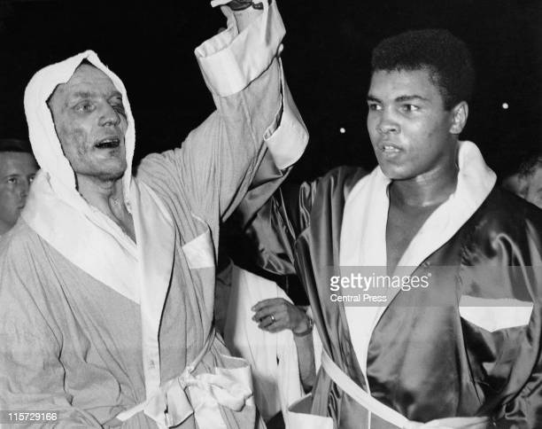 British Heavyweight champion Henry Cooper with American boxer Cassius Clay after their nontitle fight at Wembley Stadium London 18th June 1963 Clay...