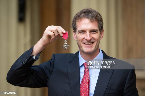 British historian and television presenter Dan Snow poses with his medal after being appointed a Member of the Order of the British Empire during an...