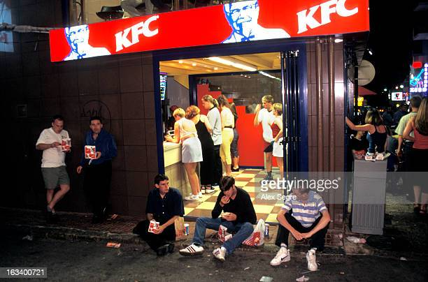 British holidaymakers eating fast food at KFC takeaway after night out in San Antonio, Ibiza