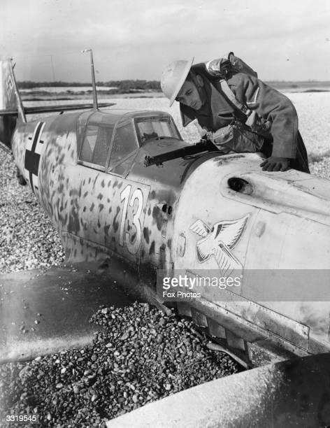 A British Home Guard soldier looks over the wreckage of a Messerschmitt BF 109E of 7 Staffel/Jagdgeschwader 54 of the German Luftwaffe piloted by...