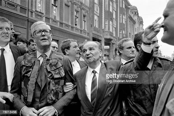British Home Secretary Douglas Hurd wearing a flak jacket is guided through the war torn streets of Sarajevo by President Alija Izetbegovic During...