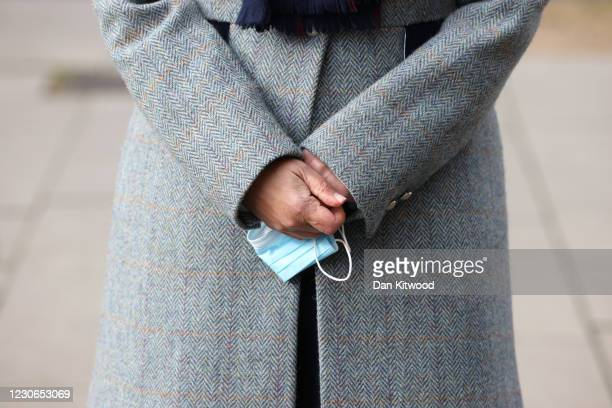 British Home Secretary Priti Patel holds her face mask as she speaks to the media outside St Thomas' Hospital on January 18, 2021 in London, England....